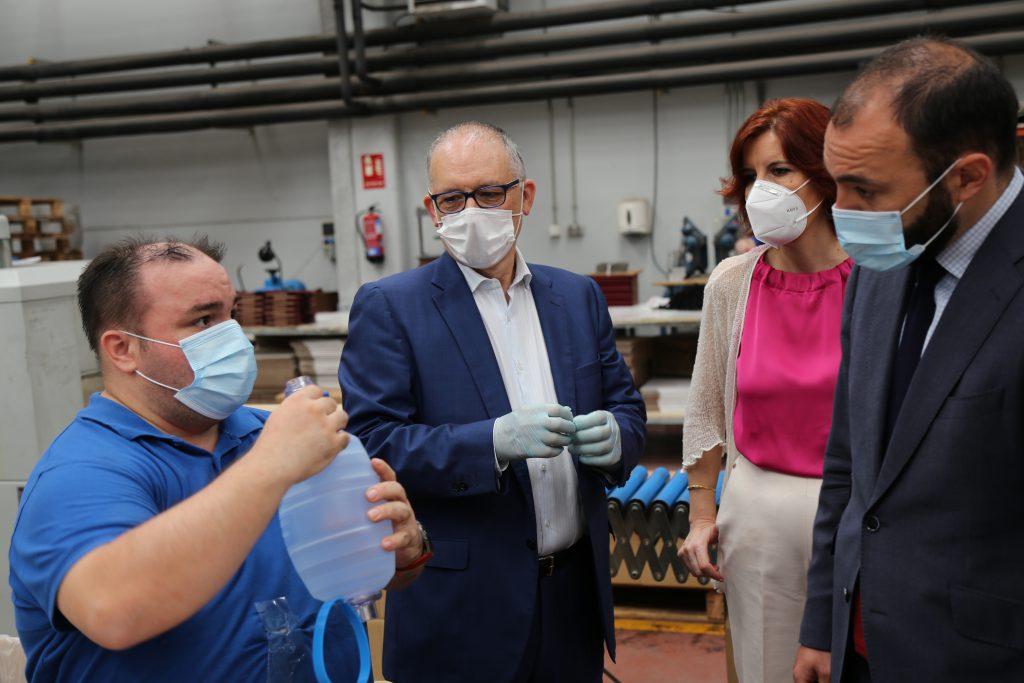 trabajador de Afanias Gráficas explica a los mandatarios de la Consejería de Empleo el proceso de fabricación. A la derecha del trabajador, Ajenadro Martínez, Presidente de Afanias